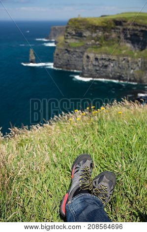 Cliffs of Moher, Ireland, rocky sea shore, legs in hiking shoes
