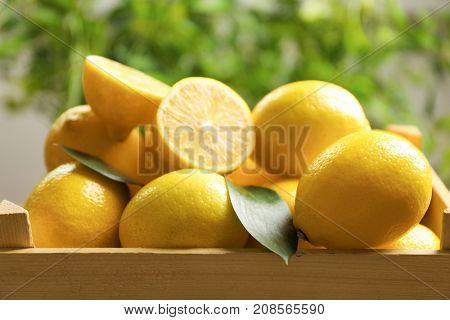 Wooden crate with fresh lemons, closeup