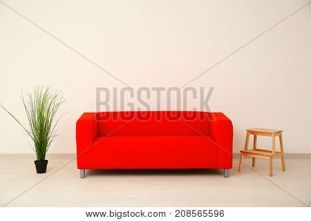 Comfortable red sofa, houseplant and step ladder near light wall