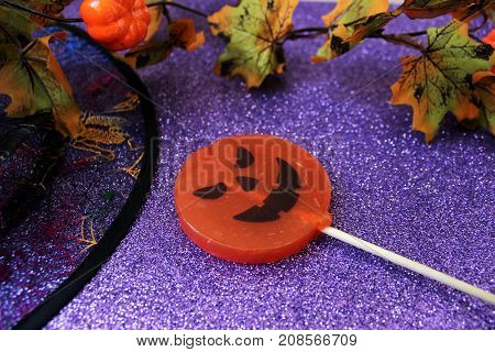 Candy in the form of a pumpkin for Halloween on the brilliant background with decorations for Halloween. Halloween background.