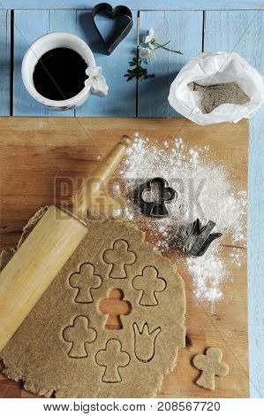 Reduced gingerbread pasta with a cup of coffee on a blue wooden surface. Christmas preparing conception.