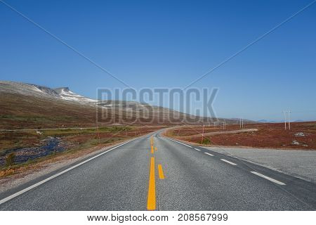 Empty road in northern Norway on a cloudless day.