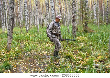 hunter with shotgun walking in the wetland forest