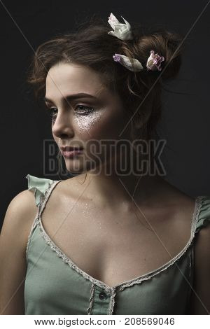 Portrait of beautiful woman with sparkles on her face. Girl with art make up and flowers in hair