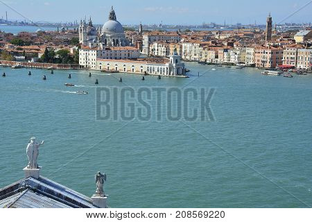 The view from the top of the bellltower of San Giorgio Maggiore church in Venice. Part of the church's roof can be seen in the foreground with Punta Della Dogana and the church of Santa Maria Della Salute (Saint Mary of Health) in the background.