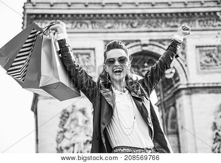 Stylish autumn in Paris. smiling elegant woman in sunglasses with shopping bags in Paris France rejoicing
