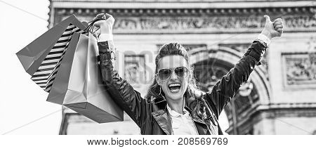 Stylish autumn in Paris. smiling modern fashion-monger in trench coat with shopping bags in Paris France showing thumbs up and rejoicing