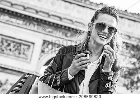 Stylish autumn in Paris. smiling trendy fashion-monger in sunglasses with shopping bags near Arc de Triomphe in Paris France having coffee and macaroon