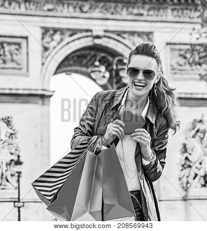 Stylish Valentine's Day in Paris. smiling trendy woman in trench coat with shopping bags near Arc de Triomphe in Paris France showing heart shaped box of chocolates