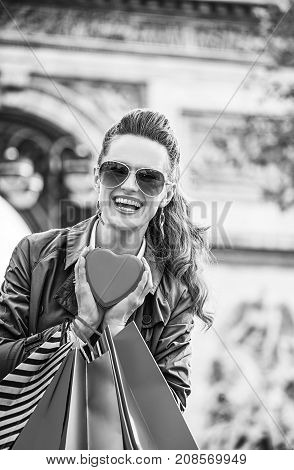 Stylish Valentine's Day in Paris. Portrait of happy trendy woman in sunglasses with shopping bags near Arc de Triomphe in Paris France showing red heart shaped box of chocolates
