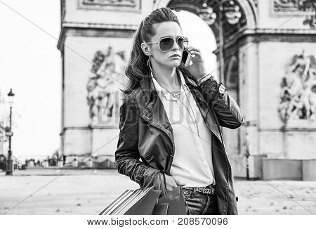 Stylish autumn in Paris. elegant fashion-monger in trench coat with shopping bags near Arc de Triomphe in Paris France using a mobile phone