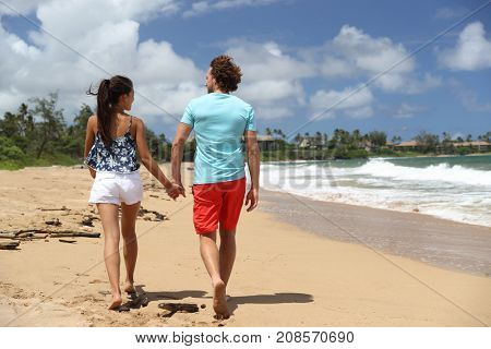 Hawaii couple walking on Kauai beach on summer travel vacation. Tourists people relaxing lifestyle in Kauai, Hawaii, USA.