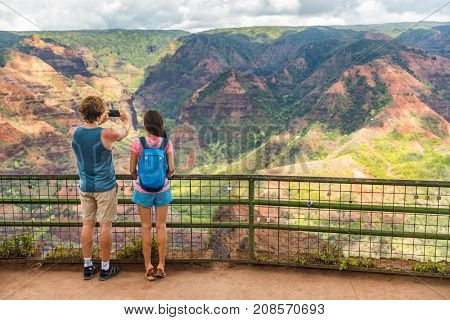 Hawaii nature hiking travel couple tourists taking photo at Waimea Canyon lookout viewpoint. Summer vacation travelers enjoying outdoor activity in Kauai, hawaiian islands.