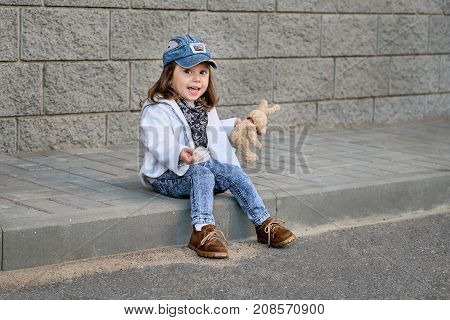 fashion girl hip hop.Model child hip - hop sitting on the steps outdoors.Portrait of a cute little girl in fashionable denim clothes.beautiful child.