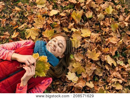 Pretty girl with long hair lying on the leaves in autumn. Girl lying in autumn with falling leaves wondering about something. Portrait of a beautiful smiling teenager. Autumn winter season.