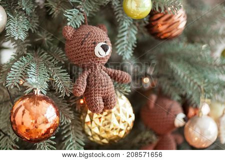 Christmas tree decorations. Toy knitted bear and vintage balls on cristmas tree. Close up shot.
