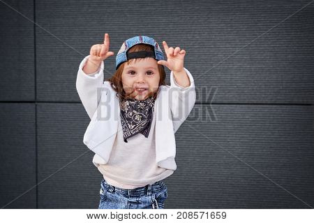 fashion baby girl hip hop.Portrait of a cute little girl in fashionable clothes.little baby girl in the baseball cap happy dancing in the background of the gray wall. child waving his hands .