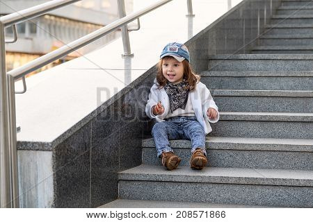fashion girl hip hop.Model child hip-hop sitting on the stairs outdoors.Portrait of a cute little girl in fashionable denim clothes.beautiful child.