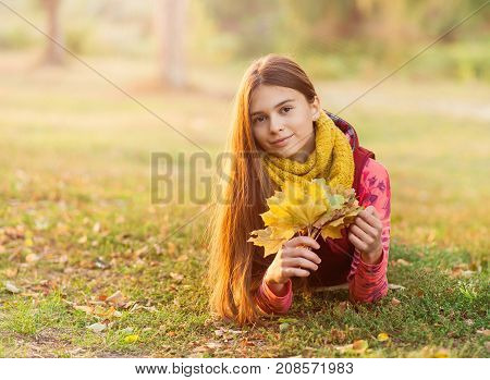 Portrait of smiling girl with leaves in her hands lying on yellow grass. Beautiful teenage girl with brown long healthy hair in the park. Autumn portrait.