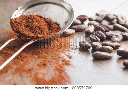 Dark cocoa powder in a sieve and cocoa beans on old kitchen table.