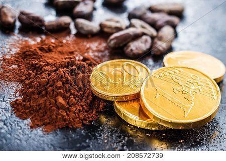 Dark cocoa powder, cocoa beans and chocolate euro coins.