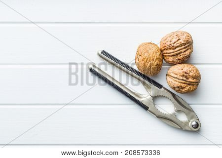 Tasty dried walnuts and nutcracker on white table. Top view.