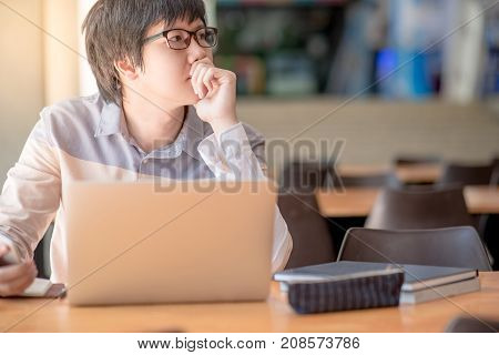 Young Asian business man feeling stressed tired and headache during working with laptop computer in public co working space. freelance lifestyle in workspace.