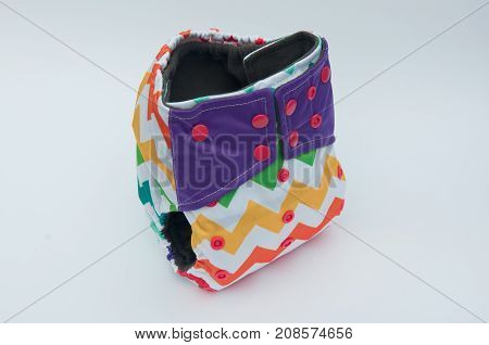 Reusable baby diaper with colorful pattern and pink buttons on white background