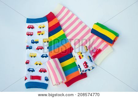 Several different size pattern cotton gaiters for babies on white background