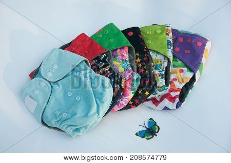 Variety of different color pattern cotton reusable diapers for babies and paper butterfly laying on light background