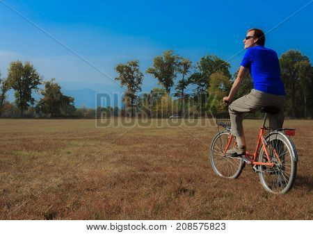 a healthy lifestyle of a fifty-years-old man practicing cycling in a park /a man exercises on a bicycle