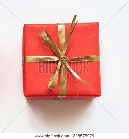 Red gift with golden bow on white background. Close up.