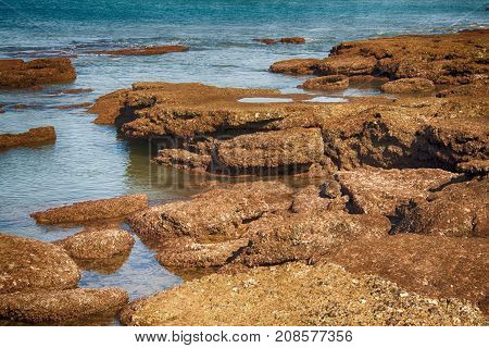 large boulders at low tide on the sea