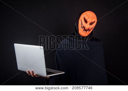 Anonymous male hacker with pumpkin halloween mask carrying laptop computer. Internet security and cyber attack concepts.