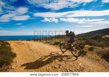 A Young Guy Riding A Mountain Bike On A Bicycle Route In Spain On Road Against The Background Of The