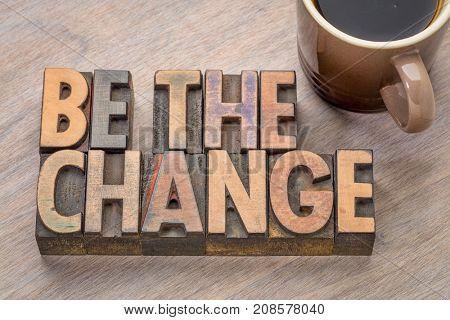 Be the change - word abstract in letterpress printing blocks with a cup of coffee