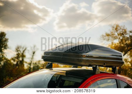 Removable black car trunk for luggage on the roof of a red car in nature in the autumn season.