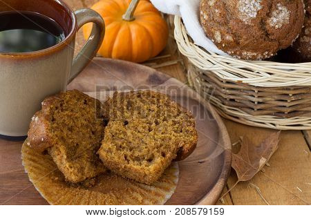 Sliced pumpkin muffin and cup of coffee on a woodem plate