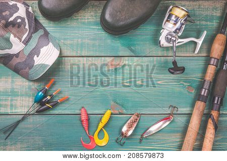 Fishing theme. background from fishing rods with fishing tackles rubber boots camouflage cap and fishing buoy on green wooden background with copy space.