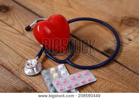 A heart with a medical stethoscope isolated on wooden background