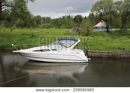 Small white motor boat moored during rainy day near camp at summer