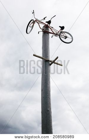 Tandem bicycle on high wooden log at cloudy day outdoor - modern art