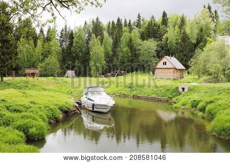 Motor boat moored during rainy day near forest with log house at summer