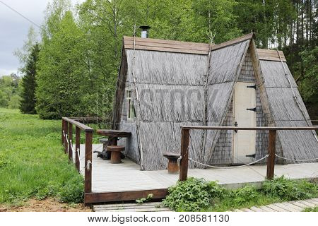 Wooden triangle house in green forest in overcast summer day