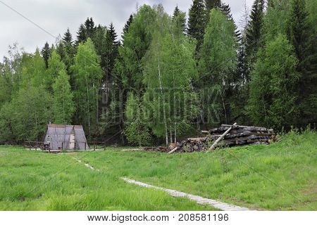 Wooden triangle small house in green forest, logs in overcast summer day