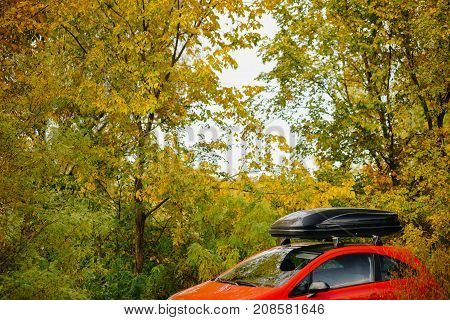 Red car with a black trunk in a beautiful autumn landscape. Departure for the city.