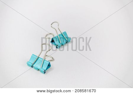 A Studio Photograph of a Pair of Turquoise Bulldog Clips