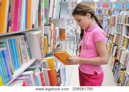 Girl with braids chooses book in large bookstore in shopping center