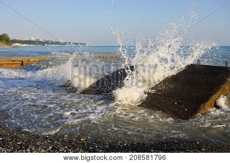 Breakwater and splashes on wave in sea shore at sunny summer day