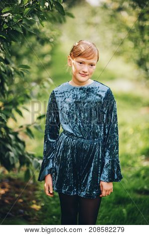 Outdoor portrait of beautiful little 10 year old girl wearing blue velvet playsuit